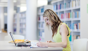 AL university student reading and studying on her own at the new library